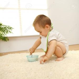 7515575-Little-baby-boy-eating-alone-on-white-carpet-Stock-Photo-floor